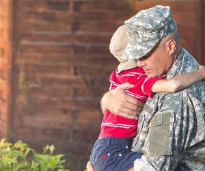 Dad in military clothes hugging young son @ PEPPERSMINT/Shutterstock.com