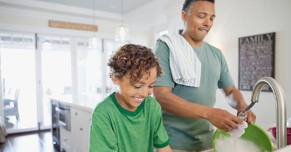 Dad and son doing dishes in kitchen | Hero Images/Getty Images