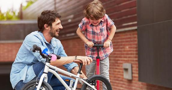 Dad and young son fixing bike's flat tire | Morsa Images/Getty Images
