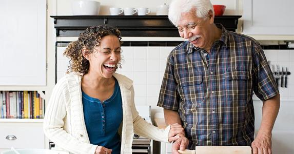 Family laughing in kitchen | Image Source/Getty Images