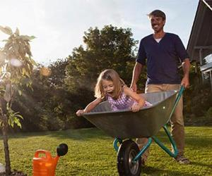 Daughter playing inside wheelbarrow with father   Westend61/Getty Images