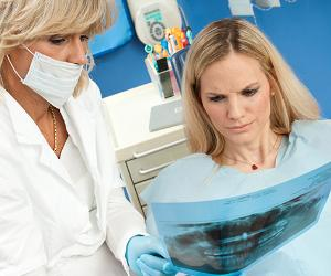 Dentist showing dental x-ray to patient © dean bertoncelj/Shutterstock.com