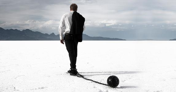 Disappointed businessman dragging ball and chain © iStock