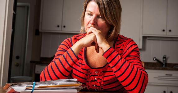Dismal woman staring at piles of bills on kitchen table | iStock.com/Fertnig