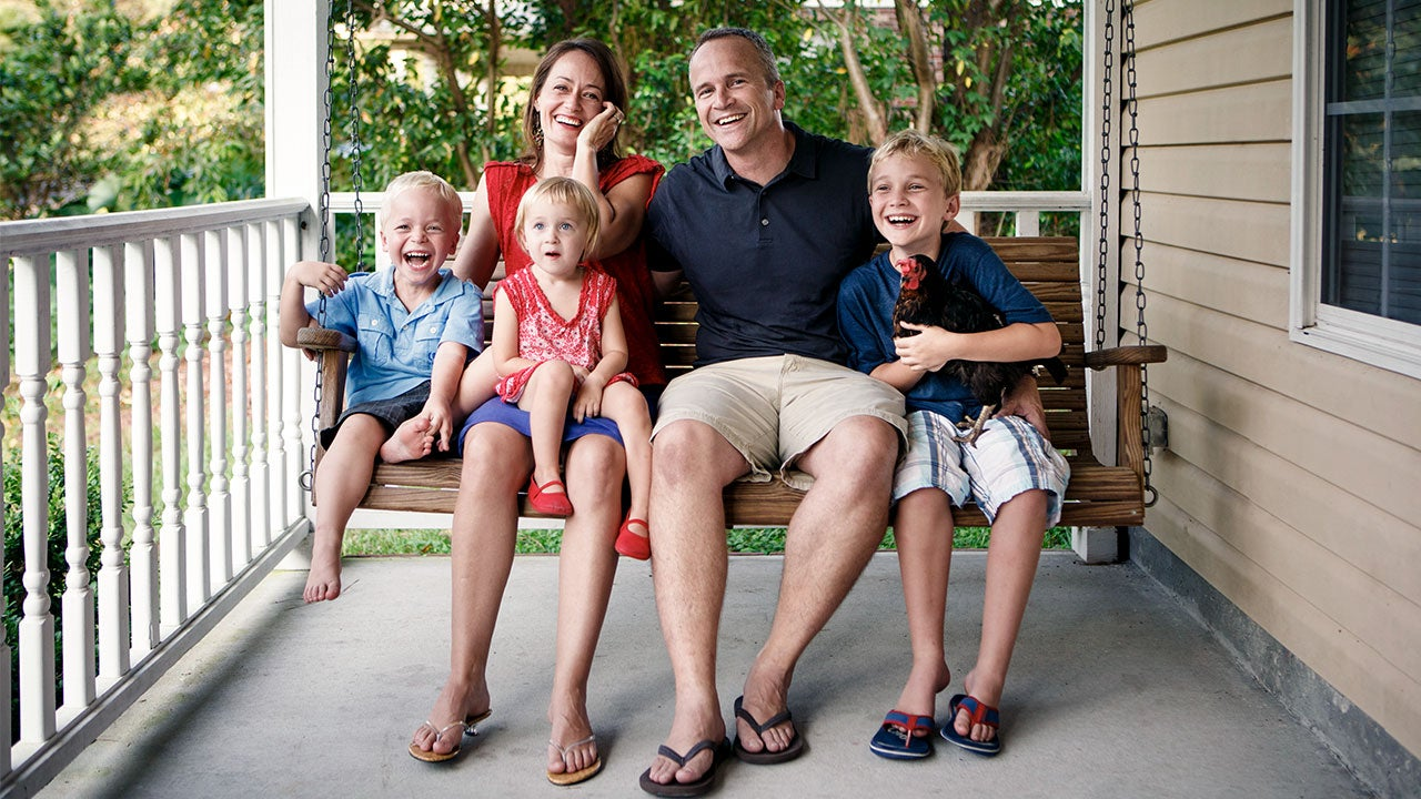 Family sitting on front porch swing | Stephen W. Morris/Getty Images