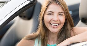 Smiling woman in convertible © Andresr/Shutterstock.com