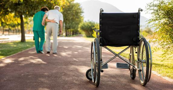 Elderly male patient walking with nurse's help © iStock