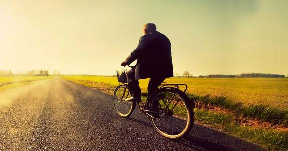 Elderly man riding a bike on road towards sunset sky © PHOTOCREO Michal Bednarek/Shutterstock.com