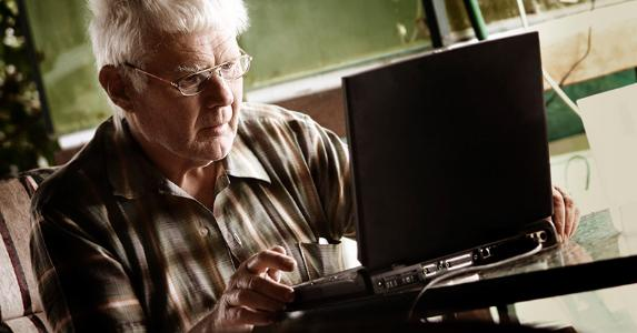Confused elderly man staring at laptop