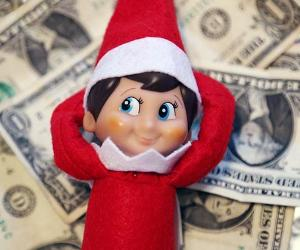 Elf on the Shelf laying on pile of money | Riley Arthur/Bankrate