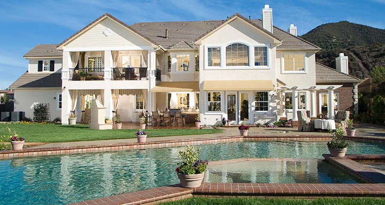 Exterior shot of mega mansion and pool © iStock