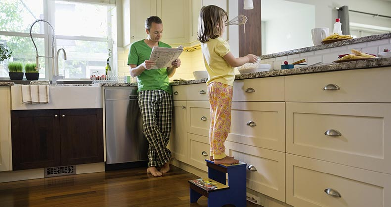 Dad and daughter in kitchen in the morning | Hero Images/Getty Images