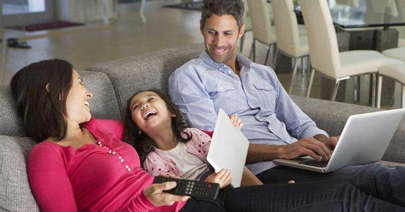 Family with their devices sitting together on couch | Monkey Business Images/Shutterstock.com
