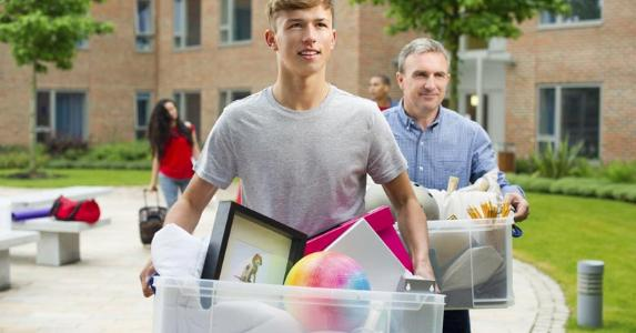 Father helping son move to college dorm