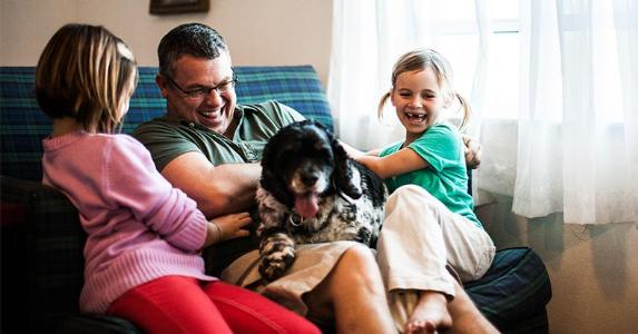 Father and kids playing with dog | MoMo Productions/Getty Images
