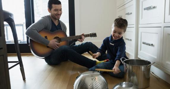 Father playing 'band' with son in kitchen | Hero Images/Getty Images