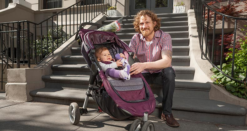 Father with his baby in a stroller, sitting on steps | Tooga/Getty Images