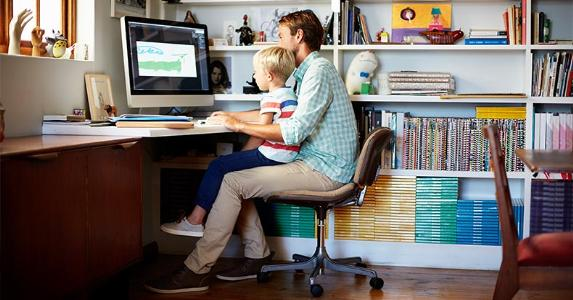 Father working from home with son on his lap | Morsa Images/Getty Images