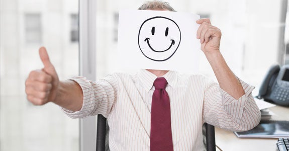 Office worker holding smiley face picture | Robert Daly/OJO Images/Getty Images