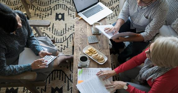 Adviser meeting with two clients at home | Hero Images/Getty Images