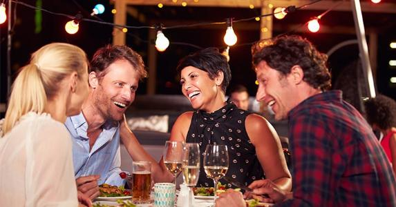 Friends laughing at dinner © MonkeyBusiness Images/Shutterstock.com