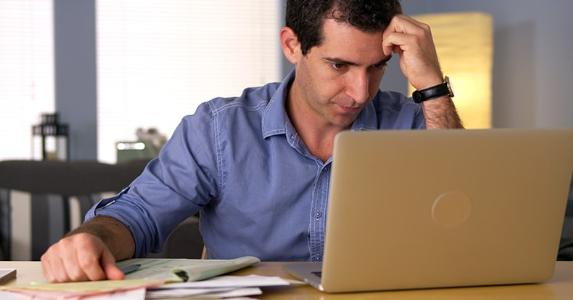 Frustrated man working on finances with a laptop © Rocketclips, Inc./Shutterstock.com