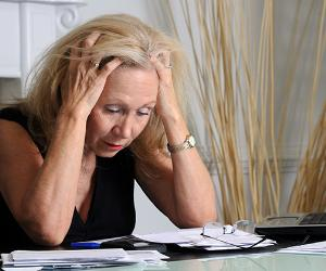 Frustrated mature woman staring at piles of bills on dining table © iStock