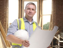 Contractor holding hard hat and blueprint
