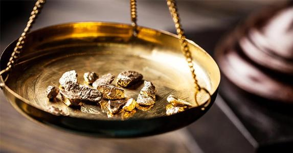 Gold bullions on scale © Billion Photos/Shutterstock.com