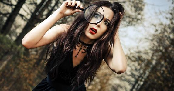 Goth woman in forest with magnifying glass © Jetrel/Shutterstock.com