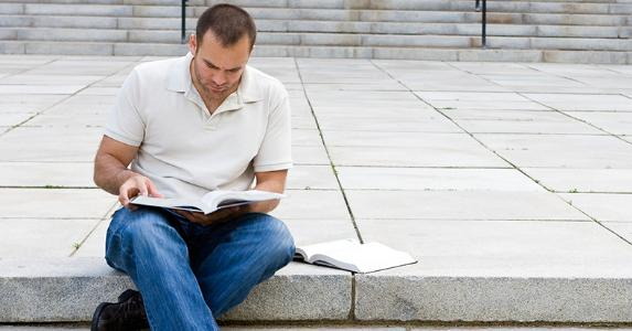 Graduate male student reading textbooks outdoors in campus