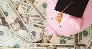 Piggy bank with grad cap on money © zimmytws/Shutterstock.com