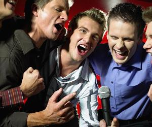 Group of men singing karaoke © iStock