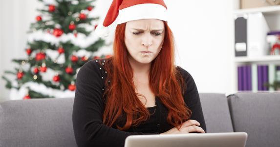 Grumpy woman wearing Santa hat © Sebastian Gauert/Shutterstock.com
