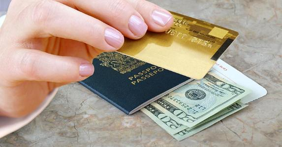 Hand holding credit card with passport and money on desk © NAN728/Shutterstock.com