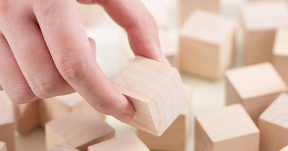 Hand picking up a wooden block © iStock