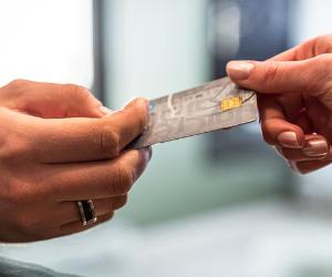 Handing over a credit card with chip | Jacek Kadaj/Getty Images