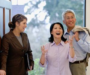 Happy couple checking house with a real estate agent | ColorBlind Images/Getty Images