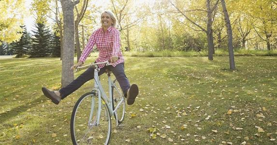 Happy mature woman riding bike in the park | Hero Images/Getty Images
