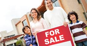 Hispanic family holding for sale sign outside  Andresr/Shutterstock.com