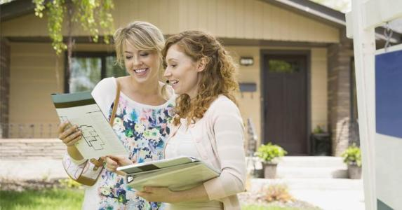 Homebuyer and her realtor outside a house | Hero Images/Getty Images