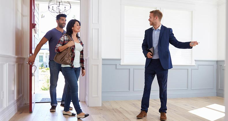 Homebuyers entering new home with agent | monkeybusinessimages/Getty Images