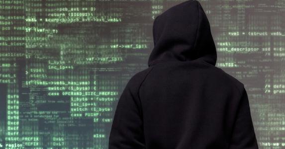 Hooded figure looking at lines of code © iStock