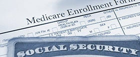 Medicare enrollment form and a Social Security card © zimmytws/Shutterstock.com