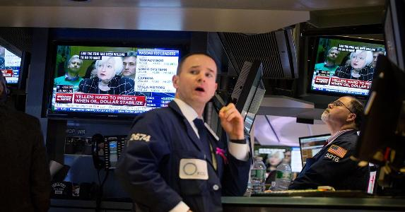 NYSE worker on floor, Janet Yellen on TV behind him | Bloomberg/Getty Images
