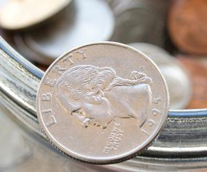 Jar full of coins with a quarter balancing on the edge © cubm/Shutterstock.com