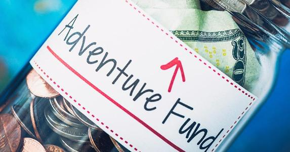 Jar labeled 'adventure fund' filled with change © iStock