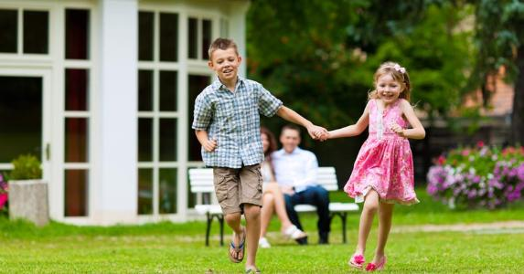 Kids running in yard | Kzenon/Shutterstock.com
