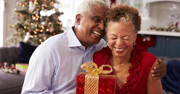Senior couple exchanging Christmas presents | Monkey Business Images/Shutterstock.com