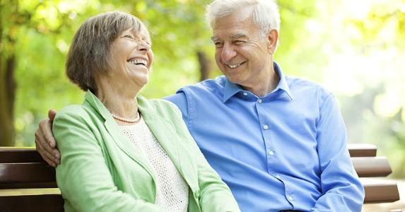 Laughing senior couple sitting on bench outdoors | alvarez/Vetta/Getty Images